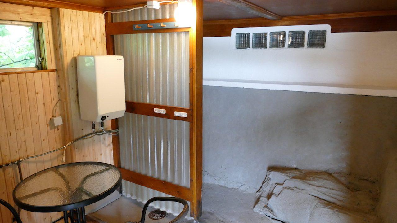 Saunavorraum mit Dusche und kleiner Sitzgelegenheit